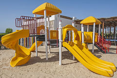 Childrens climbing frame and slide in tropical resort playground Royalty Free Stock Photography