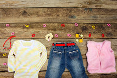 Childrens clothing and accessories: jeans, blouse, vest, hair clips, necklace and bracelet Royalty Free Stock Photography