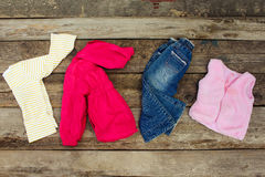 Childrens clothing and accessories: jeans, jacket, hair clips and warm vest Royalty Free Stock Image
