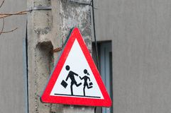 Childrens crossing warning street sign. On concrete pylon near a school Stock Image