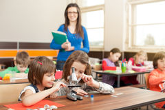 Childrens in elementary school working with teacher Royalty Free Stock Images