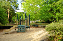 Childrens Empty Playground In The Park. Empty childrens playground in the middle of a sand pit with a park bench and surrounded by trees and scrubs Stock Photos