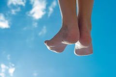 Childrens feet against the blue sky Stock Photo