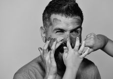 Childrens and female fingers put gouache on bearded mans face Man with happy and cheerful face expression on yellow. Childrens and female fingers put gouache on royalty free stock image