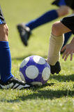 Childrens Football - Soccer. Several set of feet trying to control soccer ball - football royalty free stock photography