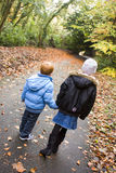 Childrens friendship. Boy and Girl walk in park surrounded by autumn leaves and trees Stock Images