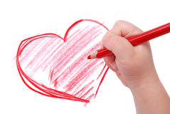 Childrens hand with pencil draws the heart Stock Photos