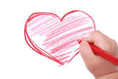 Childrens hand with pencil draws the heart Stock Image