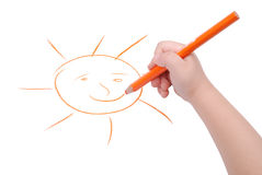 Childrens hand with pencil draws the sun Stock Image