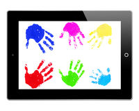 Childrens hand prints on tablet. Colorful children's hand prints on computer tablet screen, white background Royalty Free Stock Photography