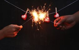Childrens hands holding bengal light blurred sparklers. On black wooden blackground and red hearts hanging on the rope stock images