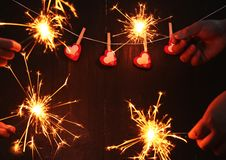 Childrens hands holding bengal light blurred sparklers. On black wooden blackground and red hearts hanging on the rope royalty free stock images