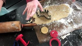 Childrens` hands making unicorn shaped christmas cookies. With metal cutter. Close-up stock video