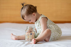 Childrens hands with money in glass jar. Close up Royalty Free Stock Photos
