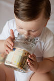Childrens hands with money in glass jar Royalty Free Stock Image