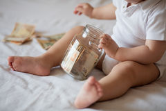 Childrens hands with money in glass jar Royalty Free Stock Photography