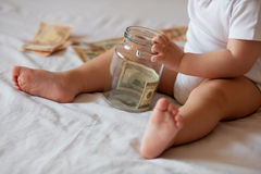 Childrens hands with money in glass jar Stock Photography
