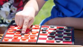 Childrens hands play checkers in the nature stock footage