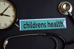 Childrens Health on the print paper with Healthcare Concept Inspiration. alarm clock, Black stethoscope. stock images