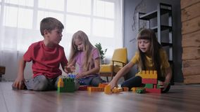 Childrens party, joyful friends have fun playing with color constructor build creative buildings from blocks of