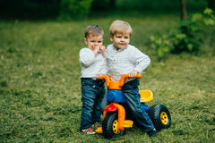 Childrens play and ride a bicycle Royalty Free Stock Photography
