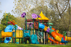 Childrens playground. A colourful childrens playground equipment with tree background Royalty Free Stock Photos