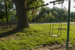 Childrens playground on the yard in summer. Rest with little child. swing in the park.  stock photo