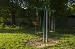Childrens playground on the yard in summer. Rest with little child. swing in the park.  royalty free stock image