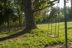 Childrens playground on the yard in summer. Rest with little child. swing in the park.  royalty free stock photo