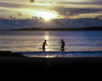 Childrens Playing in the Sea at Sunset Stock Images