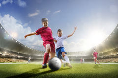Childrens are playing soccer on grand arena Royalty Free Stock Photos