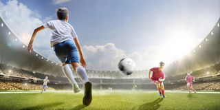 Childrens are playing soccer on grand arena. In sunlights Stock Image