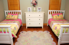 Childrens' Room. A little girls' bedroom has two twin size beds with flowers and a pretty rug Royalty Free Stock Photo