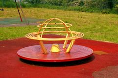 Childrens Roundabout. In a grassed play area with swings in the background Stock Images