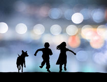 Childrens running with puppy Stock Photo