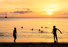 Childrens silhouette playing soccer on sunset at Tarrafal beach Stock Photo