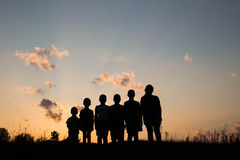 Childrens are standing on the field with sunset background Stock Photos