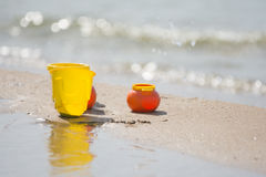 Childrens toy dishes items left on sandy shore by the water Stock Photography