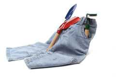 Childrens toy garden tools and a blue jeans Stock Photos