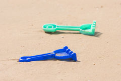 Childrens toy rake lying on sand Stock Images
