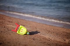 Childrens toy wheelbarrow on the beach Royalty Free Stock Images