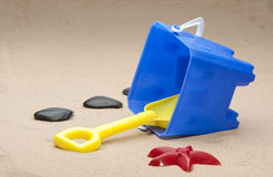 Childrens toys on sandy beach. A selection of childrens toys including a bucket and spade, laying on a sandy beach Royalty Free Stock Photo