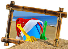 Childrens toys and Santas hat  in bamboo frame Stock Photos