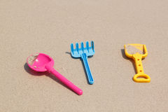Children's toys - spoon, fork and spade on sand beach Stock Image