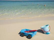 Childrens toys on a tropical ocean beach Stock Photos