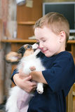 childs смотрят на лизать щенка стоковое изображение