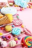 Καραμέλες με τη ζελατίνα και τη ζάχαρη ζωηρόχρωμη σειρά διαφορετικών γλυκών και απολαύσεων childs στο ροζ στοκ φωτογραφίες