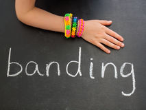 Childs arm with loom band bracelets on a blackboar Stock Image