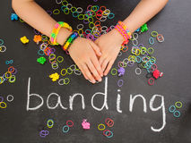 Childs arm with loom band bracelets on a blackboar Stock Images
