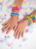 Childs arms wearing multicoloured bracelets Stock Photo